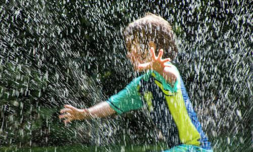 child-running-through-the-water-sprinkler-randall-nyhof